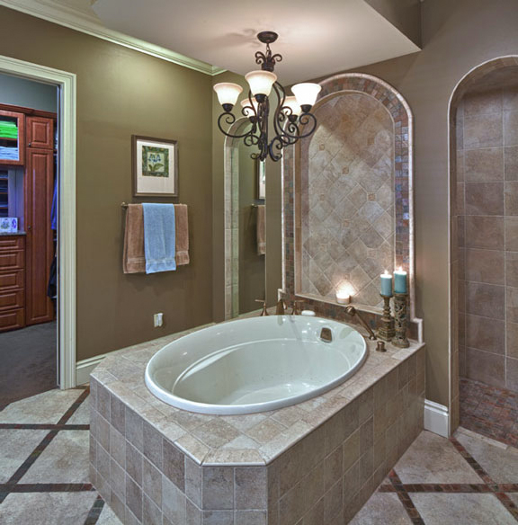 The soaker tub is the highlight of this master bathroom. Arches are carried out from the shower entrance at the right, the tiled feature over the tub, and the mirror on the left. The spacious master's closet can be seen to the left.