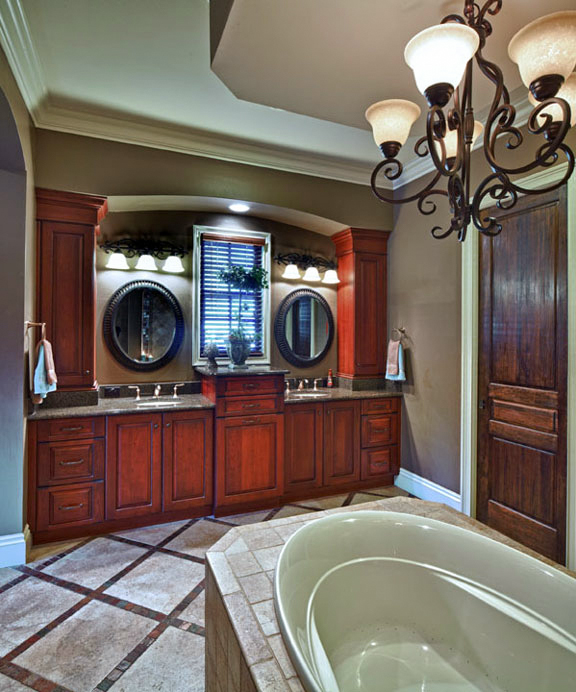 Tile inlays and chandelier add formality to the en suite bathroom. Double sinks are flanked by tower cabinets for plenty of concealed storage to avoid clutter. The master's closet is location through the door on the right.