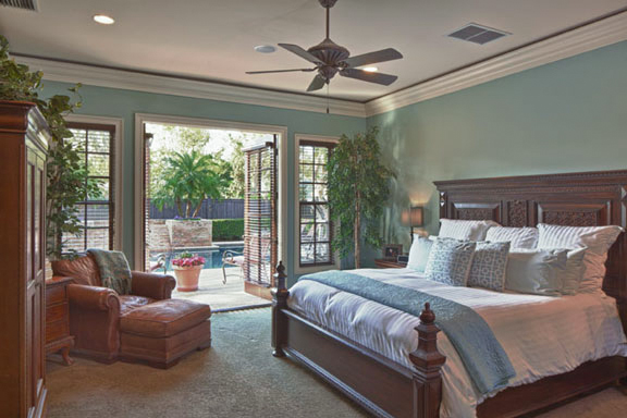 Painted in a soothing shade, the master bedroom has a clear view and access to the pool, spa and waterfall.