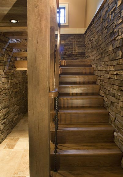 The basement is accessed by descending a staircase of hickory exposed wood stair treds. The staircase is surrounded by waist-high stone walls, and an iron and wood rail.