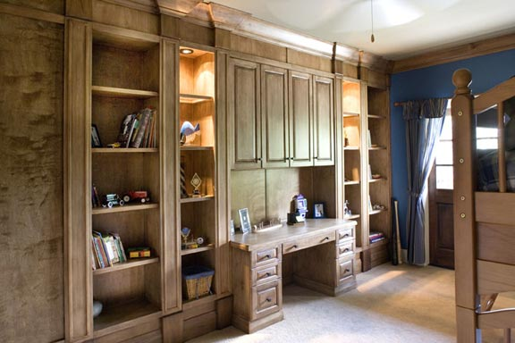 The masculine boy's room features built-in bookcases, desk, French doors leading to a private balcony, and a private bathroom.
