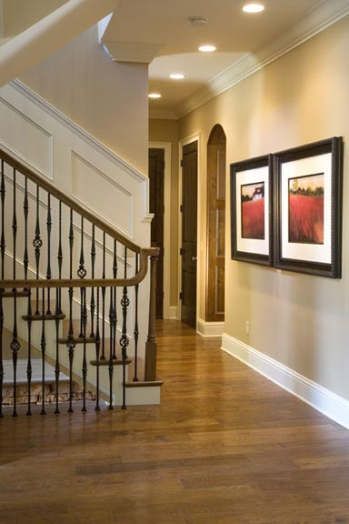 The spacious hall in the foyer features hickory flooring, paneled and arched doorways, and wainscoting. The open staircase leads to the upper floor as well as the basement.