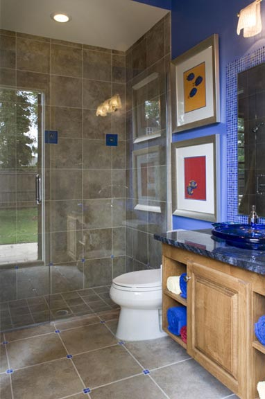 Connecting the media room with the outdoor living area, the Caribbean blue pool bath incorporates glass tiles into the floor and serves as a frame for the sink mirror. The blue glass vessel basin helps create a lively multi-purpose bathroom. Blue glass tiles in the shower were acquired on a family trip to California.