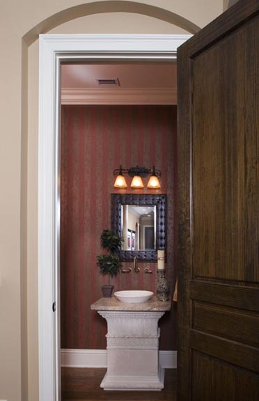 Located off the entry hall, the powder bath stunningly displays a cast stone pedestal sink with vessel basin.