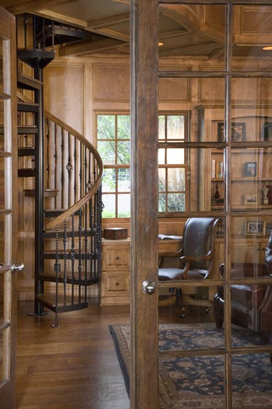 The custom-made spiral staircase leads to a book loft with floor-to-ceiling bookcases and hidden passages.