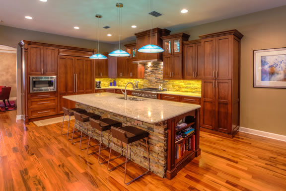 The large island accommodates seating for four and provides additional storage space on the opposite side. It is accented with stack stone, a granite countertop, and a bookcase handy for cookbooks.