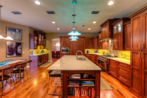 Adjacent to the kitchen is the beverage center that includes a sink, beverage refrigerator, and additional storage space.