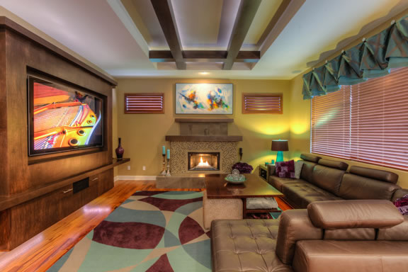 The family room features a floating built-in entertainment center constructed from maple, with storage below. The raised ceiling is accented with maple beams and up-lighting.