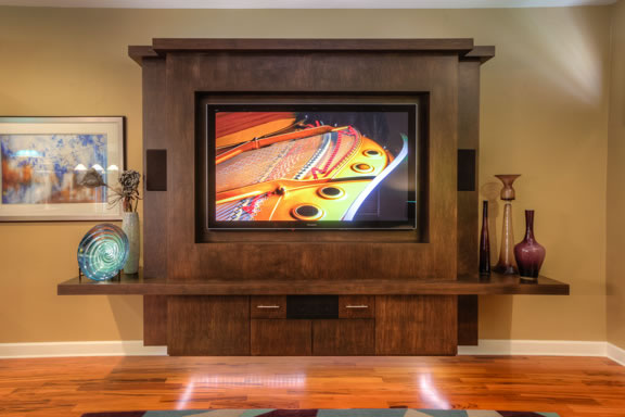 The floating built-in entertainment center is constructed from maple, with storage below and single shelves that showcase prized artwork.