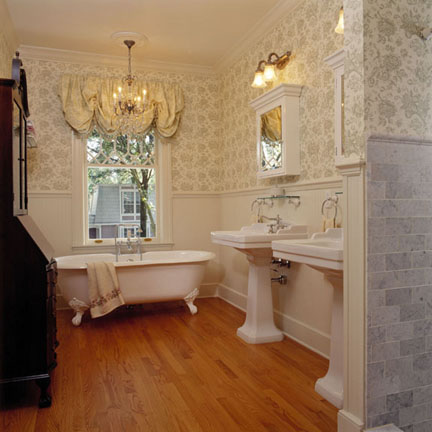 "The bathroom conveys an early 20th century look with bead board wainscoting, wood flooring, 6"" baseboard, pedestal sinks and marble- tiled shower."