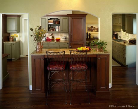 An elegant archway opens the kitchen to the dining area. A counter and bar stools are used for casual dining.