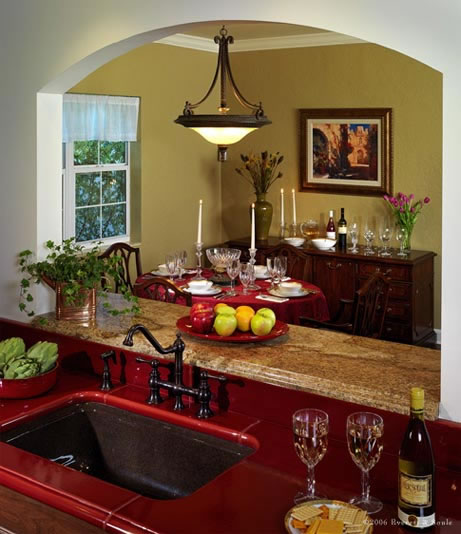 A pass-through arched window was designed to visually open the areas and connect the kitchen and dining room. A deep burgundy Lavastone counter accents the deep bronze colored sink.