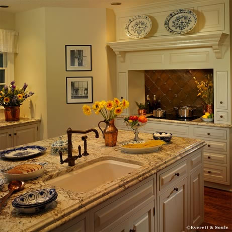 Favoring subdued tones, the homeowner selected a cream speckled granite countertop. Rustic style fixtures adequately accent the island's prep sink.
