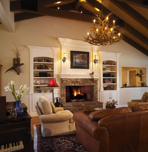 Stacked stone used on the front of the house was repeated on the fireplace in the family room. New built-in bookcases and a fireplace surround are painted warm white and blend more effectively with the existing wood floor, tongue-in-groove vaulted ceiling and exposed beams.