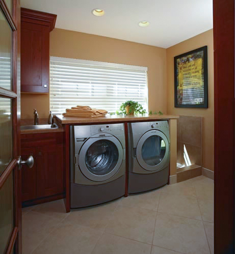 The state-of-the-art front-loading washer and dryer are topped with a laminated counter. An adjacent stationary tub has a matching top and is encased in the cabinetry that matches the kitchen cabinetry. A powder room is tucked into the space to the left, and the mini tub to the right of the washer and dryer is equipped with a shower head for easy clean up of everything from pets to muddy shoes.