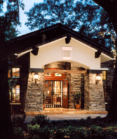 The rustic hunting lodge theme was carried out on the exterior by combining a stone facade, custom iron entry gate and built-in entry doors crafted of solid imported mahogany with inlaid stained glass.