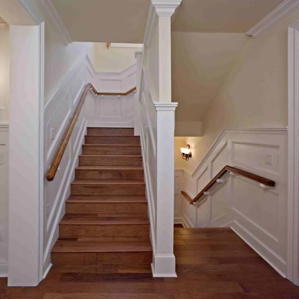 The staircase to the upstairs and to the basement is richly detailed with painted chair railing, hand rail supports, and wainscoting that beautifully contrasts with the wood stairs. The stair treds are finished with fluted edging.