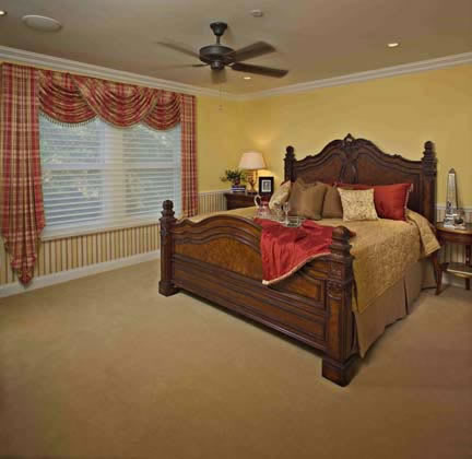The spacious master bedroom upstairs is decorated in contrasting hues fit for a southern lifestyle.