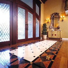 Guests step into a foyer highlighted with a stunning wood floor that is inset with patterned marble.