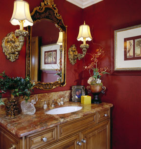 The powder room is pristinely appointed with marble countertop, custom cabinet and rich wall covering.