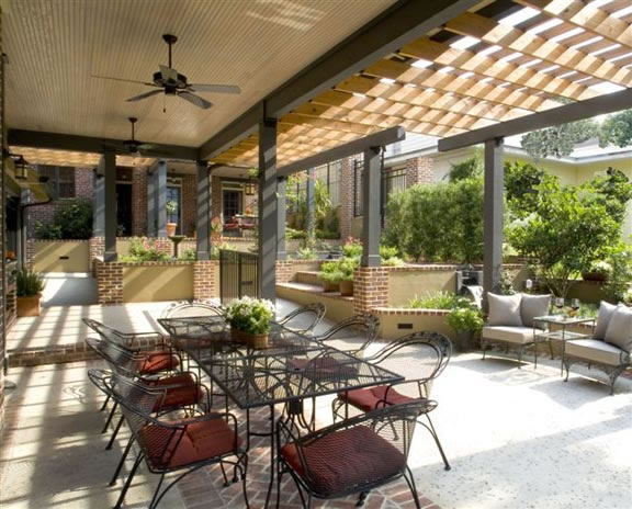 The dining and intimate seating areas on one of the mid-level decks are shaded overhead with cypress trellises.