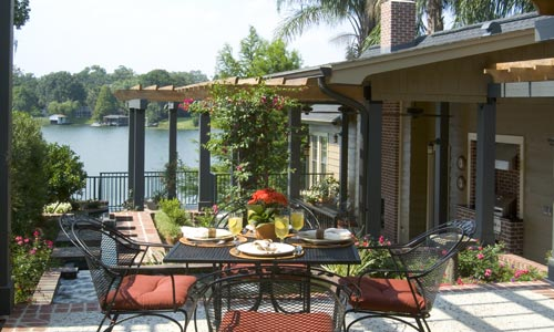A mid-level seating area is gently shaded overhead by cypress trellises. Brick is used on the stairs and perimeter of entertaining areas. In the background is an ideal view of the lake.