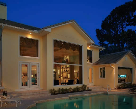 Magnificent two story windows dominate the dramatic rear elevation which, in the evening, serves to showcase the home's interior to the world while providing those inside with a perfectly framed view of the pool, lake and fireworks display from Disney.
