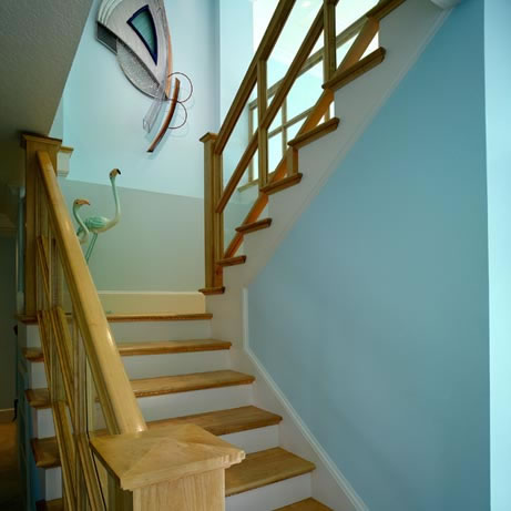 The former spiral staircase was replaced and moved to the opposite side of the great room and crafted from select white oak and poplar woods with tempered, tinted glass inserts at the open sides of the stairway and handrail. Rope accent lighting at the stair treads provides glamour and safety for the owner, who think of the stairway system as another work of art featured in their home.