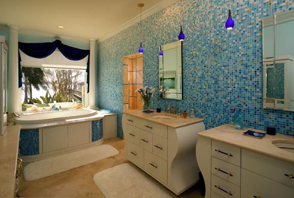Whimsical glass mosaic tile, pendant lighting and custom shaped cabinets set the tone in the delightful master bathroom. Formerly located on the other side of the home and with no direct view of the lake, the master bathroom now also encompasses a lake view through an expansive window over the luxurious tub.