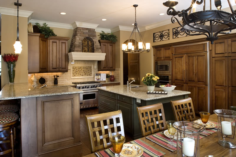 The Tuscan and Traditional style is successfully carried into the kitchen while creating a comfortable space for the family. Granite countertops, a cast stone hearth, cherry wood cabinets, and iron inlays are featured. Kitchen appliances include a GE Monogram raised dishwasher, microwave and refrigerator, a six-burner Viking stove, drinking water dispenser, and concealed walk-in pantry. A large island provides both seating and work space.